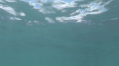 Underwater shot of Surfer sitting on his surf board waiting   Stock Footage