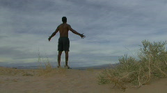Male reaching his arms out in the desert Stock Footage