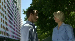 Male and female talking under trees near an office Stock Footage
