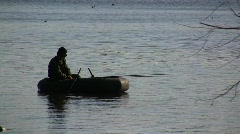 A lonely fisherman in an inflatable rubber boat fishing with a rod  Stock Footage