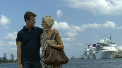 Romantic couple near a harbour with cruise ship in background Stock Footage