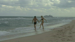 Couple holding hands walking along a beach with a cruise ship in the background Stock Footage