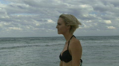 Female wrapping a towel around her on a beach Stock Footage