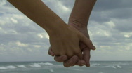Couple holding hands walking along a beach Stock Footage