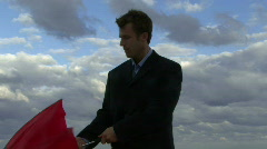 Cu of a male opening an umbrella on a beach and checking if it is raining Stock Footage