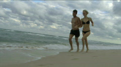 Couple running and playing on a beach Stock Footage
