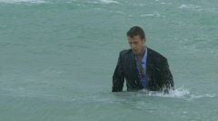 Male walking out of the ocean in suit Stock Footage