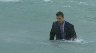 Stock Video Footage of Male walking out of the ocean in suit
