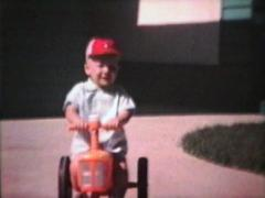 Boy Rides Tractor Outside (1964 - Vintage 8mm film) Stock Footage