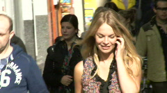 Female on phone walking through crowd in busy street Stock Footage