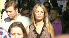 Female walking through crowd in busy street Stock Footage