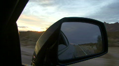 View in wing mirror as car drives through desert at sunset Stock Footage
