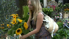 Female buying flowers on flower market and smelling them - stock footage
