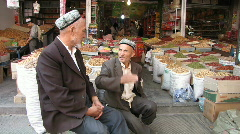 Kashgar 2 men sat outside dried fruit & spice shop Stock Footage