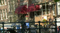 Female cycling over bridge in amsterdam and waving to friend Stock Footage