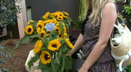 Female buying flowers on flower market and smelling them Stock Footage