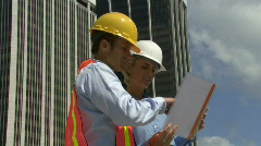 Male and female construction workers on a site - stock footage