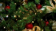 Christmas tree decorated with blinking lights red balls and golden ribbons.  Pan Stock Footage