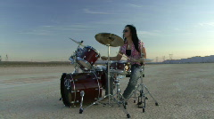Female playing drums in desert Stock Footage