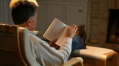Dolly right man reading book at fireplace Stock Footage