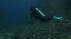 Diver swimming towards the dark edge of the reef - stock footage