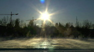 Low winter sun hangs blue sky steaming freezing icy river Stock Footage
