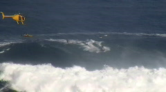 Surfer rides Jaws, huge waves, helicopter tracks. - stock footage
