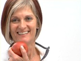 Stock Video Footage of Mature healthy female with red apple turn NTSC