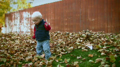 Toddler Playing in Fall Leaves 3 - stock footage