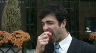 Businessman eats apple. Stock Footage
