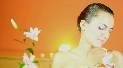 Young attractive woman gently touching the skin with a flower Stock Footage