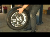 Stock Video Footage of Mechanic puts new tire on car