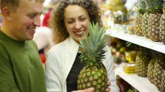 Smiling man and woman buying pineapple in supermarket Stock Footage
