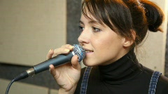 Young female vocalist with microphone singing in studio Stock Footage