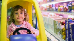 Little girl sitting in car-shopping trolley in supermarket Stock Footage