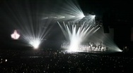 People in concert hall look at singer in light of beams Stock Footage