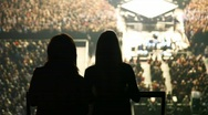 Silhouettes of two dancing women against concert hall Stock Footage