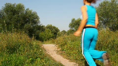 Man and woman run forward on path in park Stock Footage