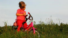 Little girl on bicycle draws on paper on field in grass Stock Footage