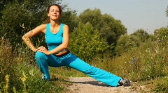 Woman carries out exercises on path in park Stock Footage