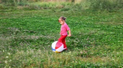 Little girl runs behind ball across the field in park Stock Footage