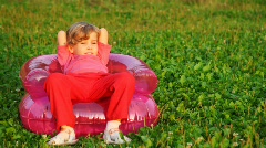 Girl rest in children's inflatable armchair on field in park Stock Footage