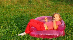 Girl sit in children's inflatable armchair, holds finger in mouth and smile Stock Footage