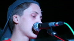 Young vocalist singing through microphone live on stage Stock Footage