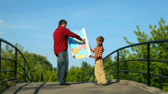Man with boy unrolling map of europe Stock Footage