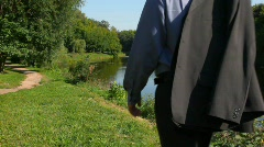 Handsome man walking along bank from camera Stock Footage