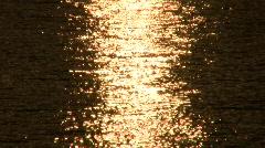 Golden light sparkles on ocean waves Stock Footage