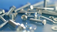 Rotating bolts and nuts on workbench. - stock footage