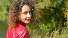 Portrait of young smiling curly-headed woman turn round at camera Stock Footage