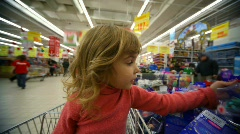 Little girl sitting in shopping trolley buying toys in mall Stock Footage